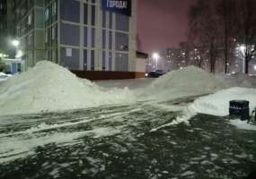 Коммунальщики складируют убранный во дворе снег около подъезда